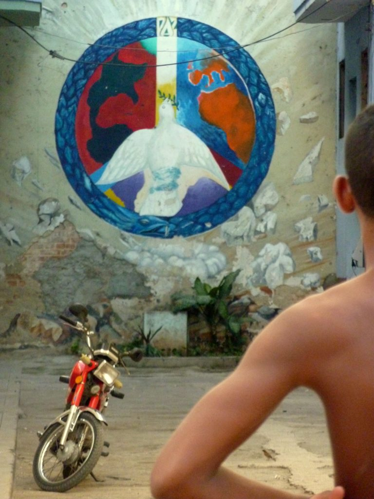 Boys playing soccer in an alley in Havana, Cuba with a peace sign in the background, courtesy of Roxanne Krystalli